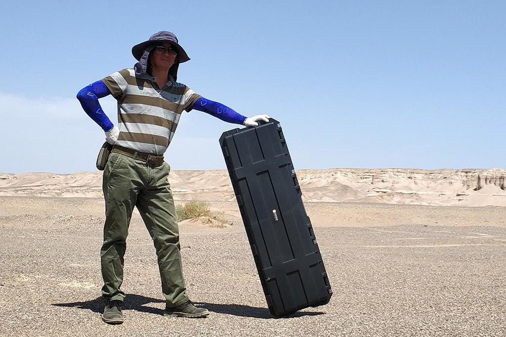Mann in der Wüste zur Expedition mit einem Outdoor Case